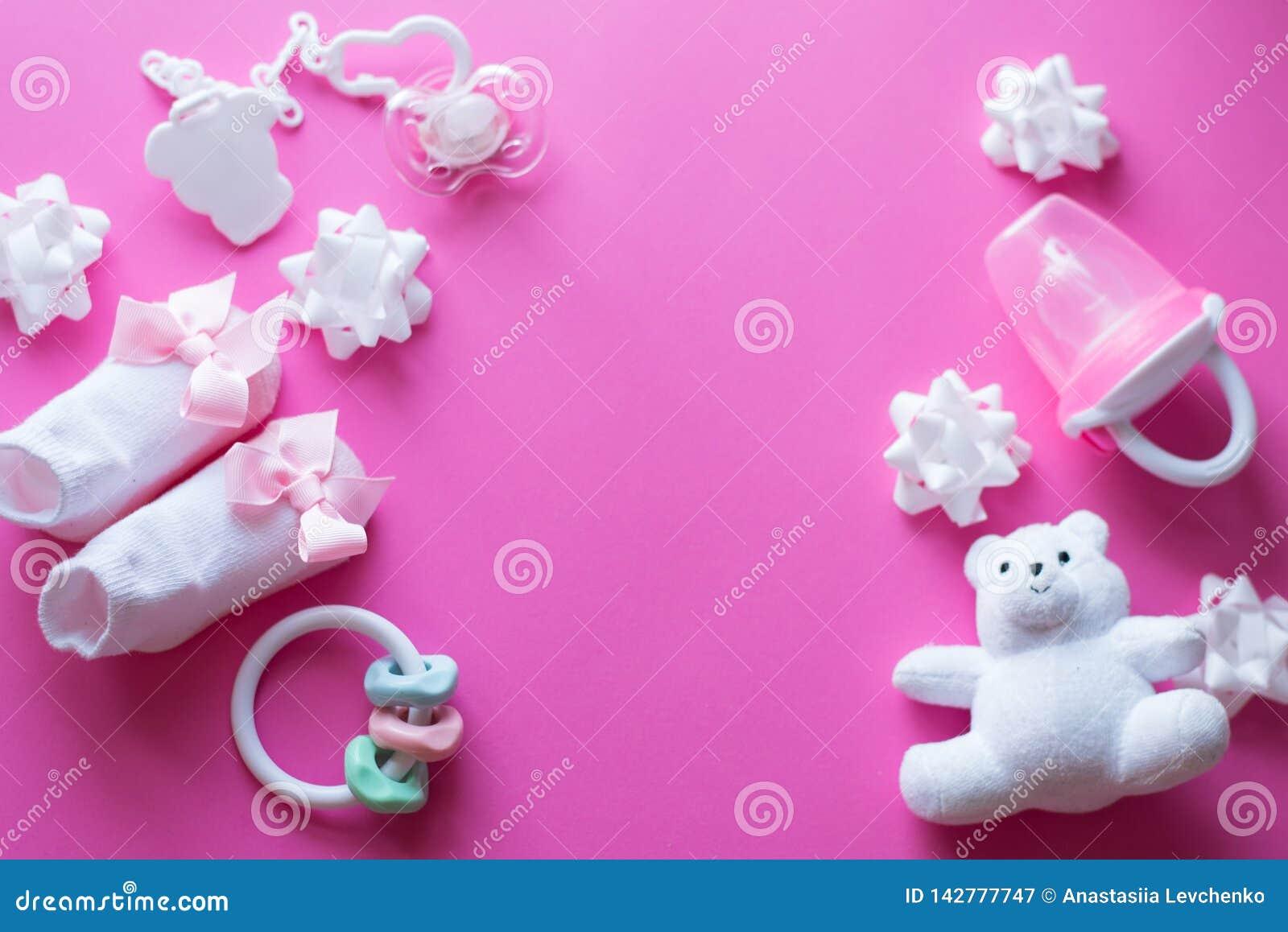 Babytoebehoren en speelgoed op roze achtergrond Hoogste mening de kindvlakte legt met wit speelgoed