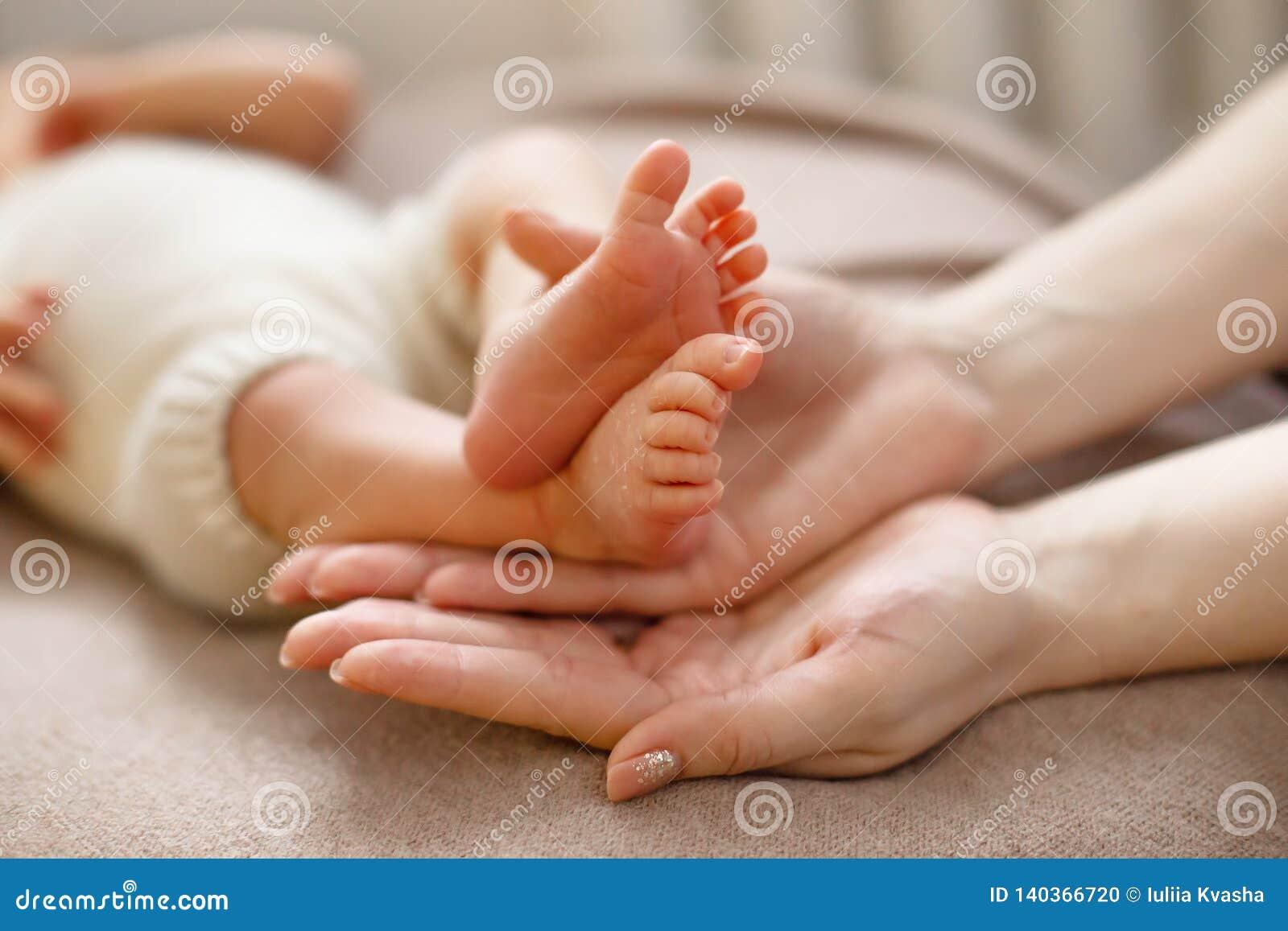 Babyvoeten in moedershanden die tot een kom worden gevormd Verzacht vage achtergrond van de voeten en de hielen van pasgeboren