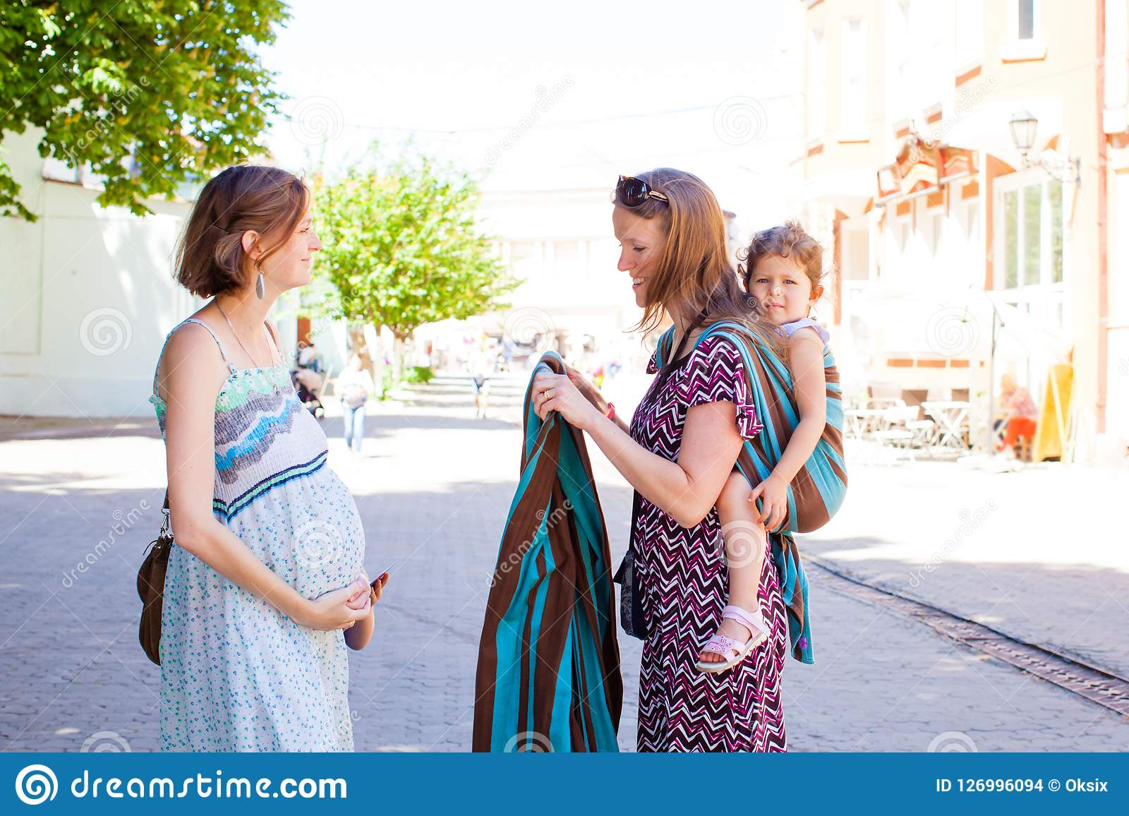 7090fcfbc6e Babywearing consultant carrying her child on her back meets pregnant lady  to teach her to use slings and baby carriers