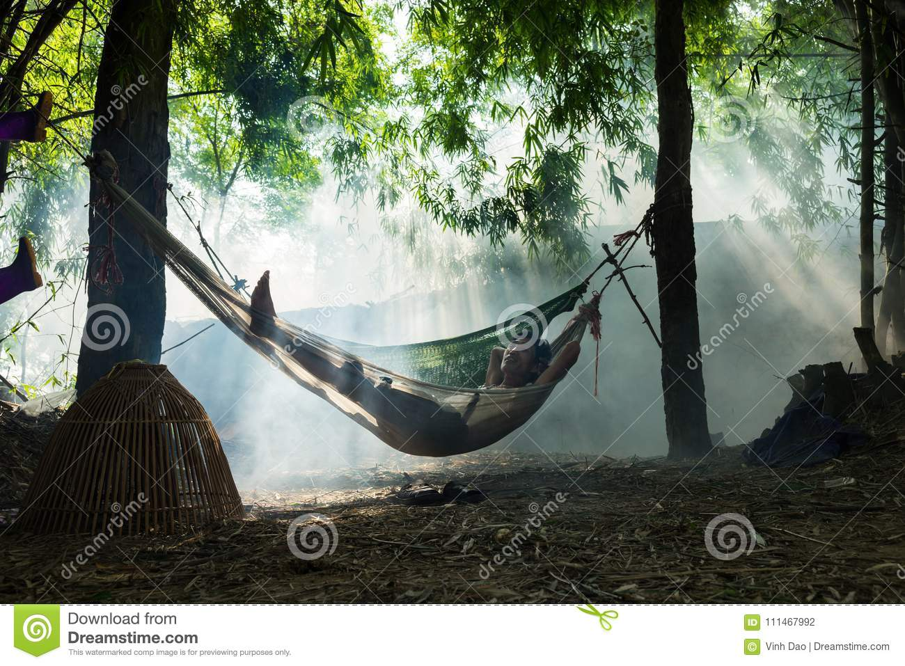 Bac Ninh, Vietnam - May 29, 2016: A man taking a break at noon on hammock in the shade of tree by Cau river