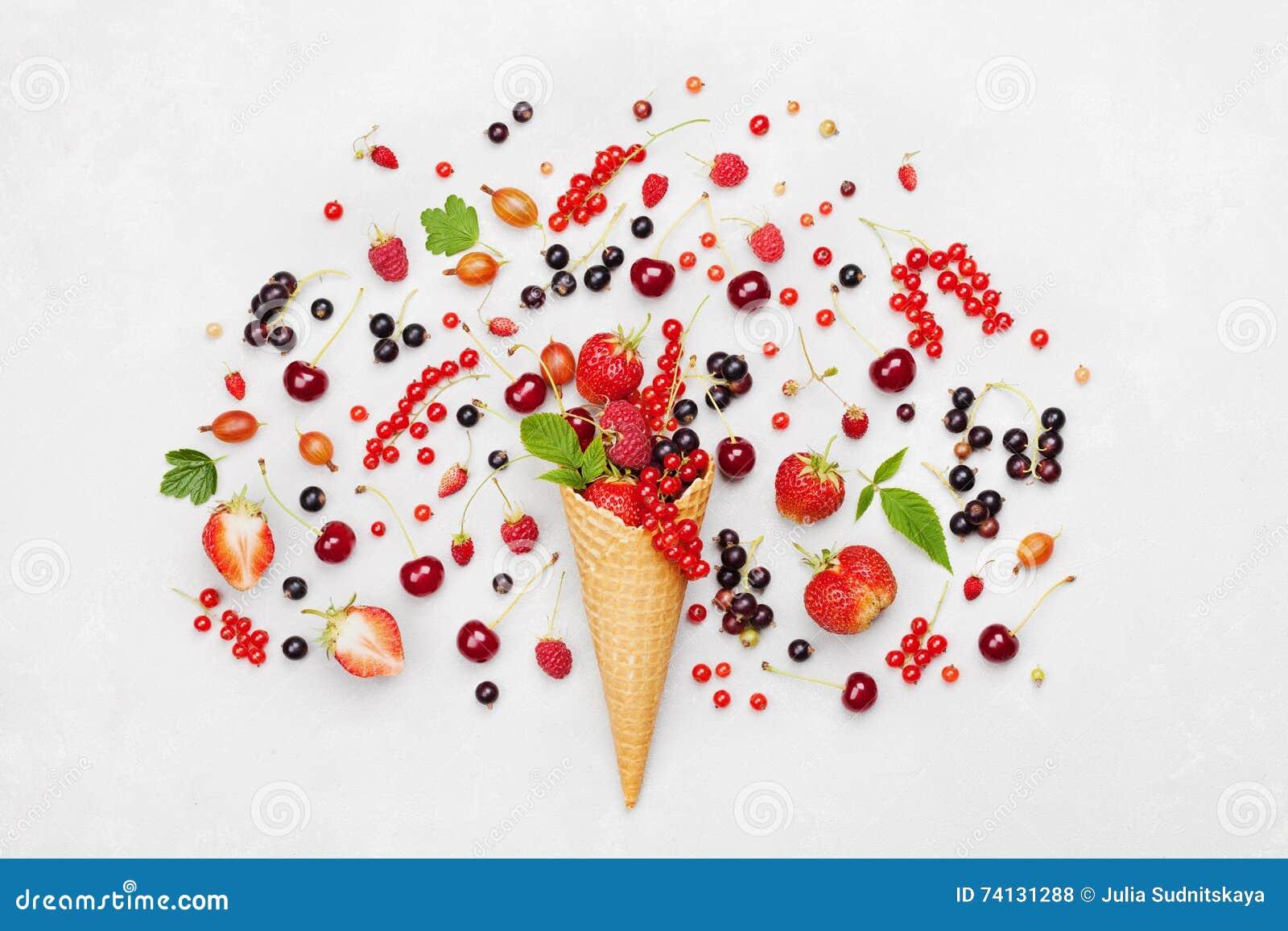 Bacche variopinte nel cono della cialda su fondo leggero da sopra Dessert dietetico e sano Designazione piana di disposizione