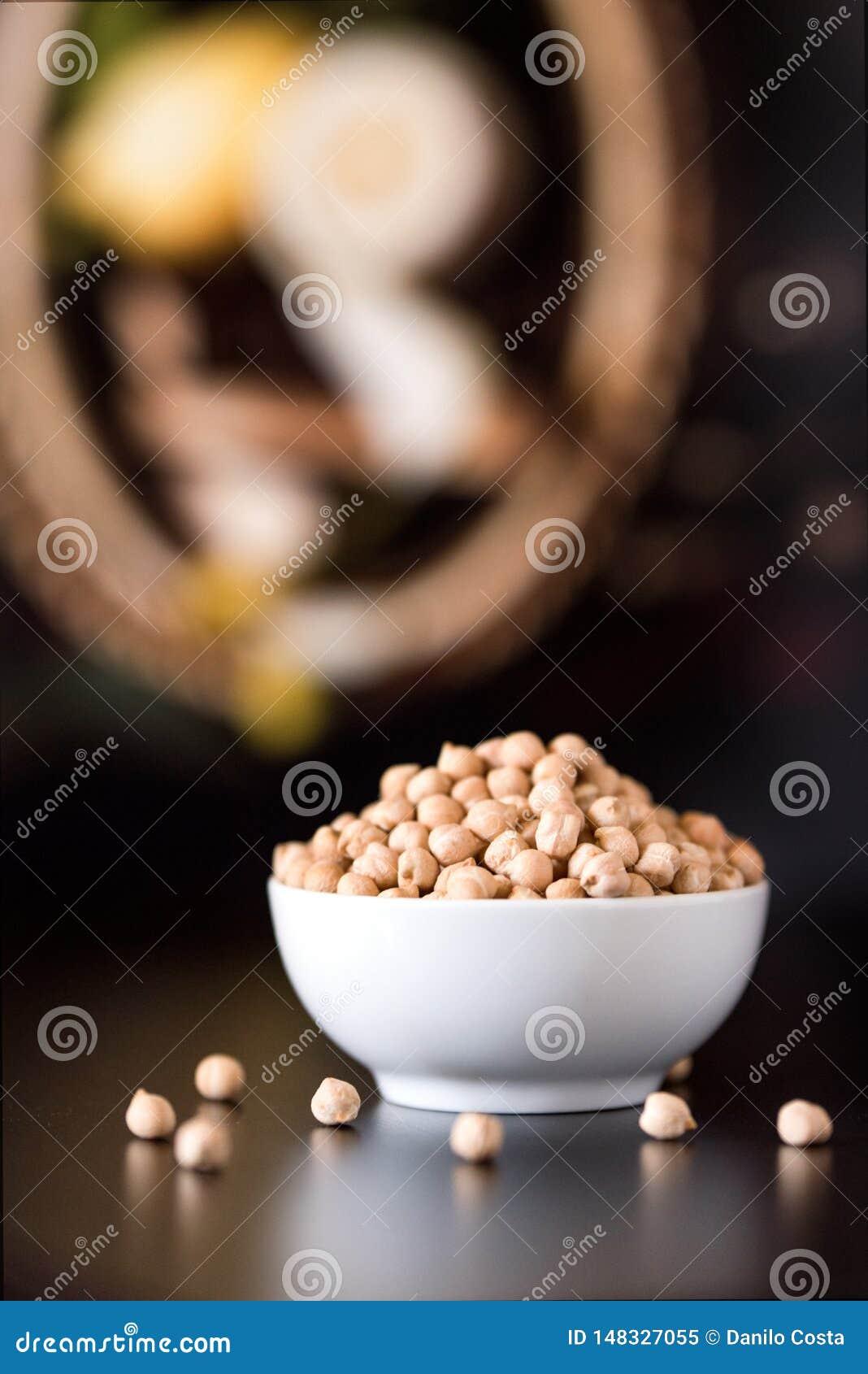 Bacia branca de grãos-de-bico crus na tabela de madeira