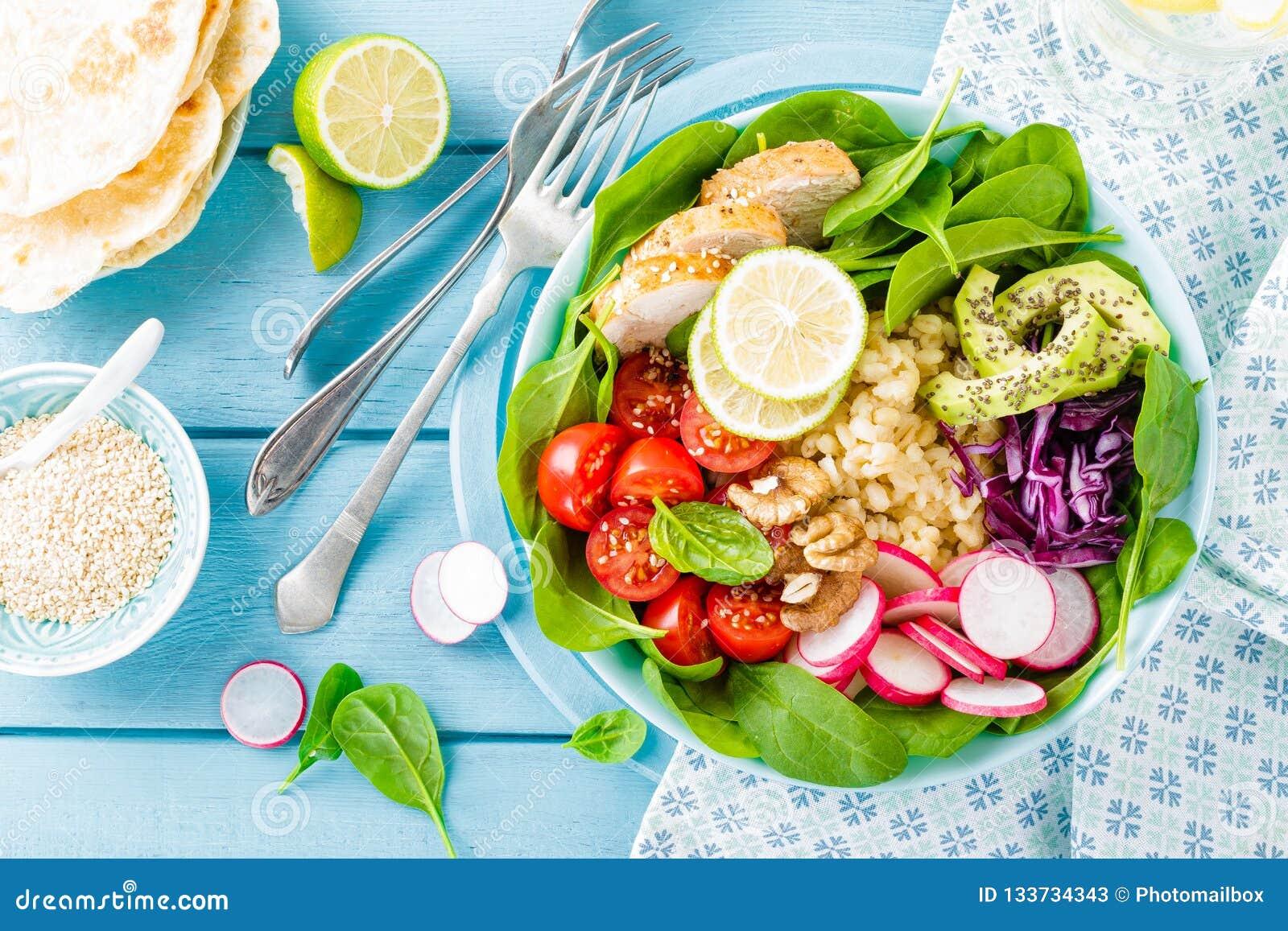 Bacia com carne da galinha, bulgur e salada grelhados do legume fresco das folhas do rabanete, dos tomates, do abacate, da couve