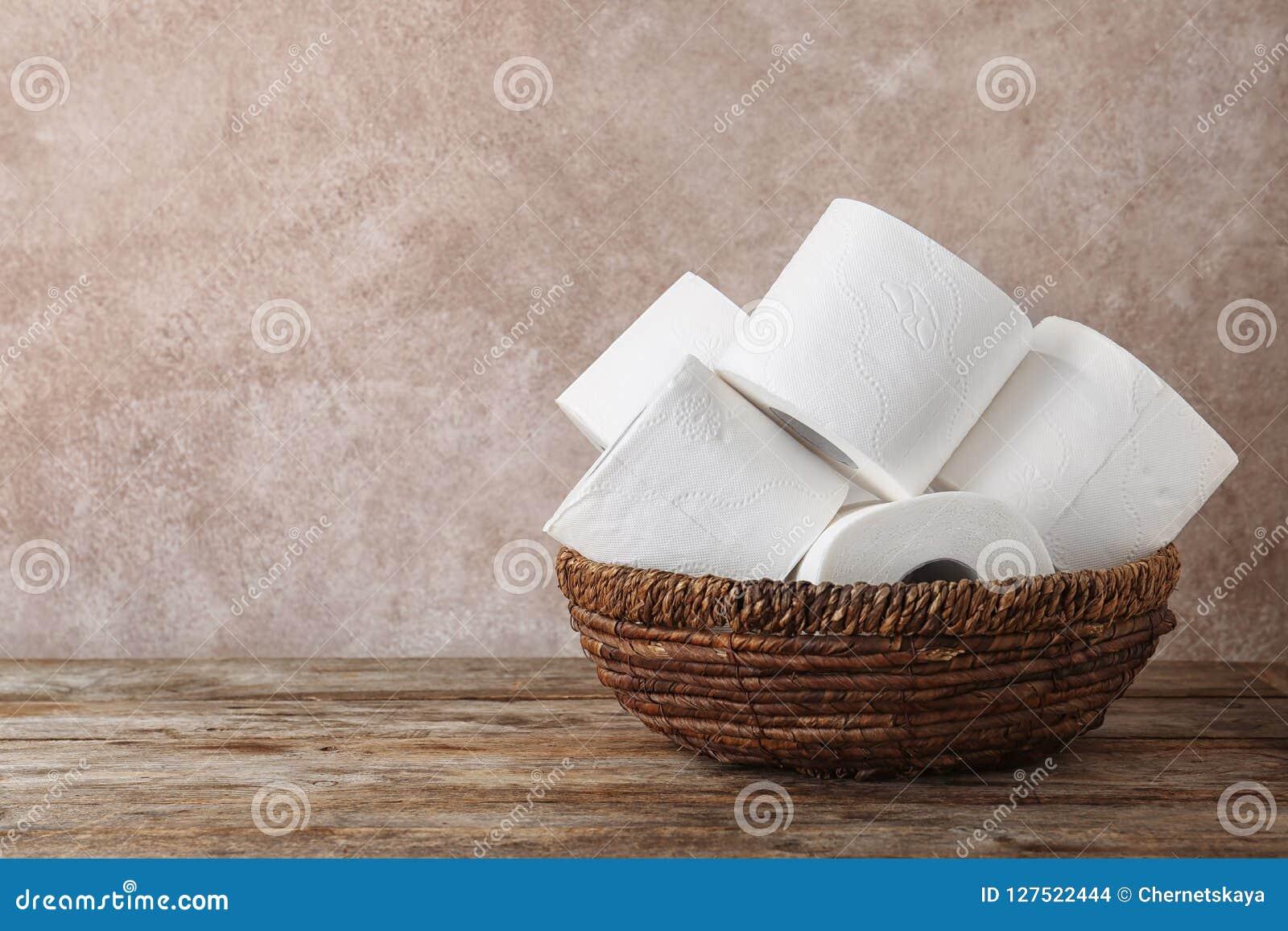 A bacia com papel higiênico rola na tabela de madeira