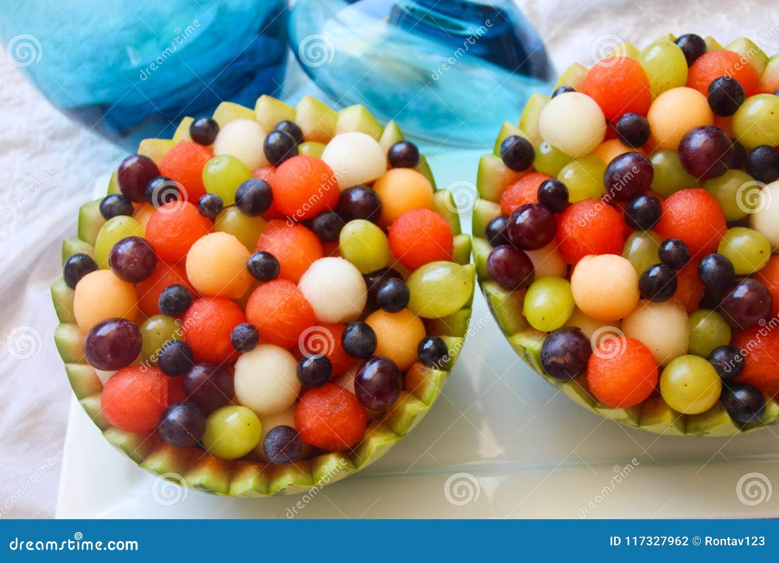 A bacia da melancia encheu-se com a melancia, as bolas de melão, uvas verdes e roxas e bagas
