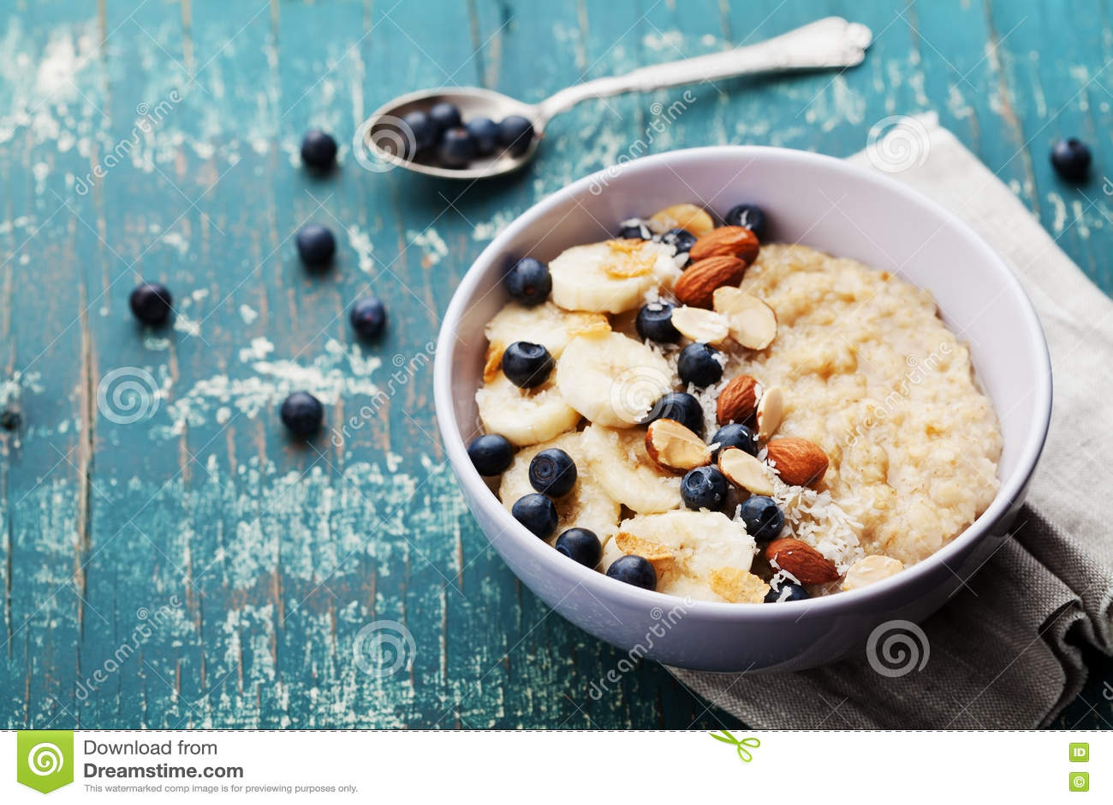 Bacia de papa de aveia fresco da farinha de aveia com molho da banana, dos mirtilos, das amêndoas, do coco e do caramelo na tabel