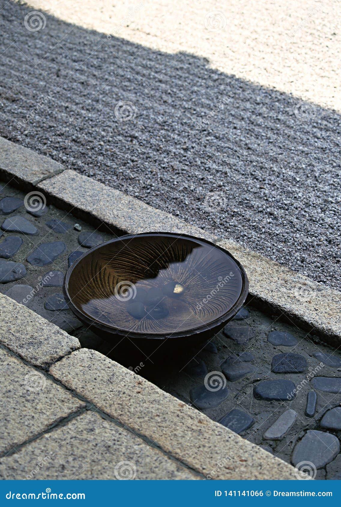 Bacia japonesa enchida com água mantida em um fundo de pedra do assoalho
