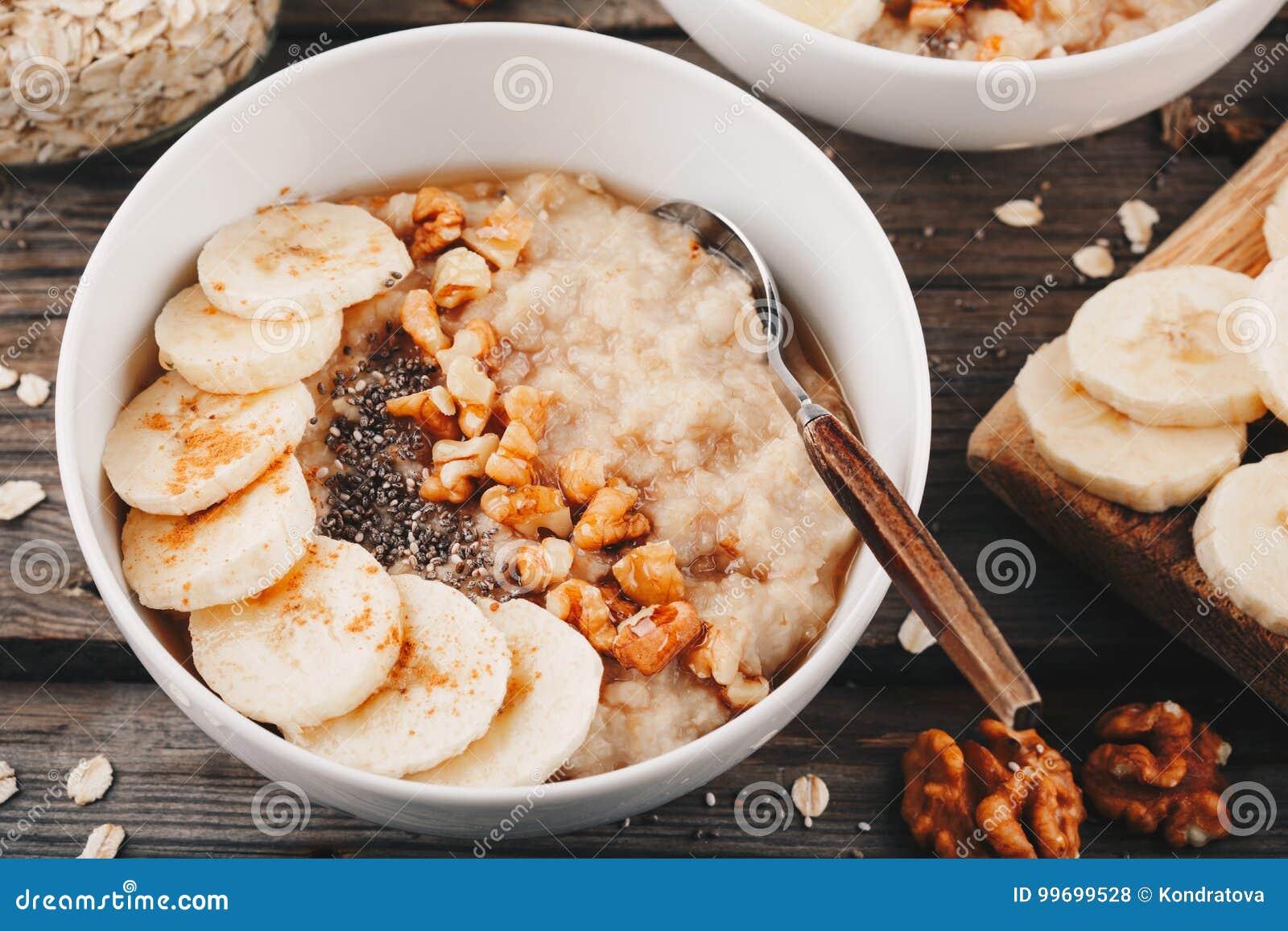 Bacia saudável do café da manhã farinha de aveia com banana, nozes, sementes do chia e mel