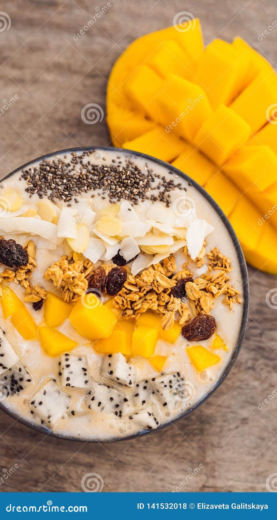 Bacias do batido feitas com manga, banana, granola, o coco raspado, o fruto do dragão, as sementes do chia e a hortelã no fundo d