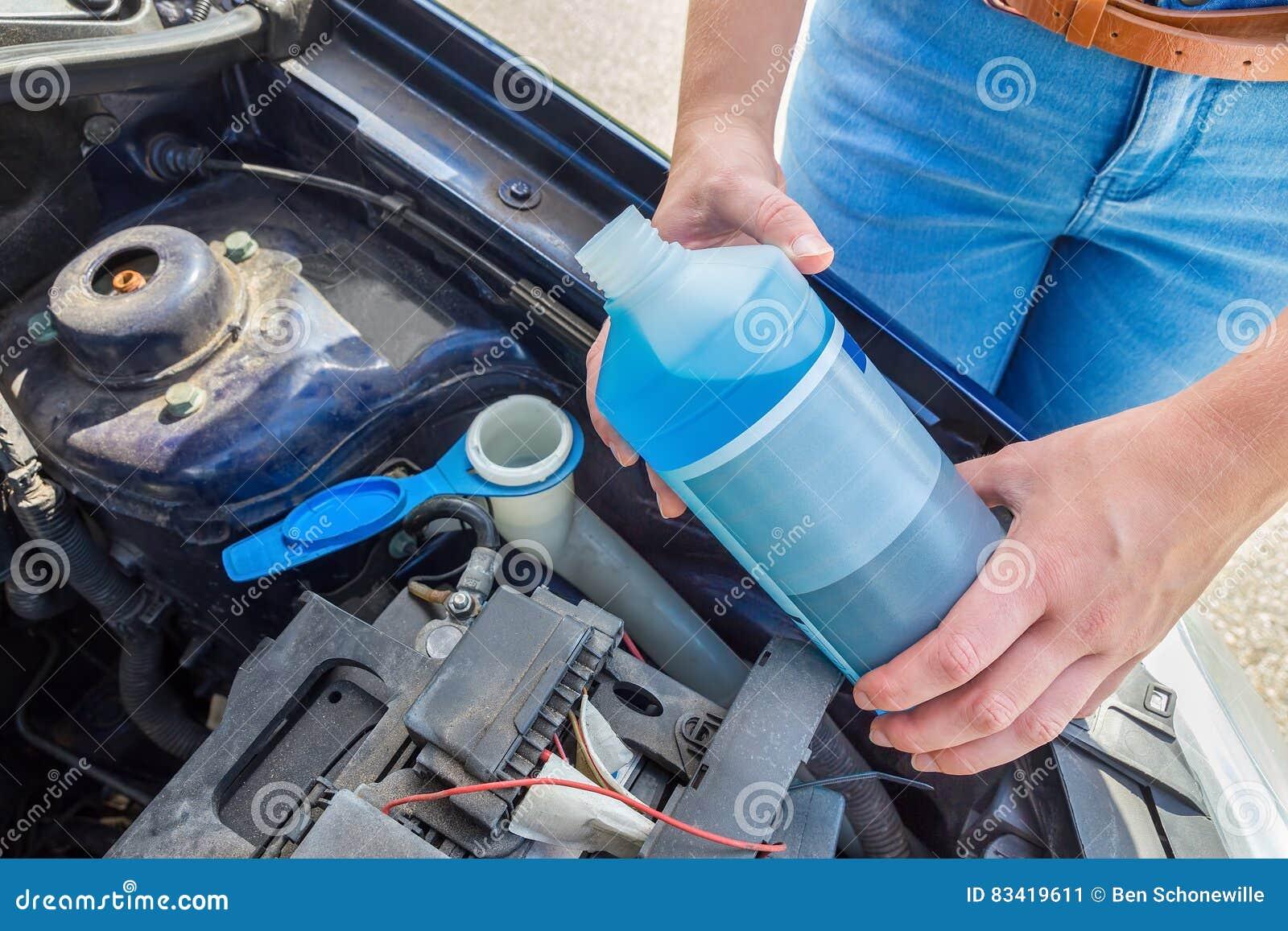 Bacino idrico di riempimento dell automobile della donna con liquido blu in bottiglia