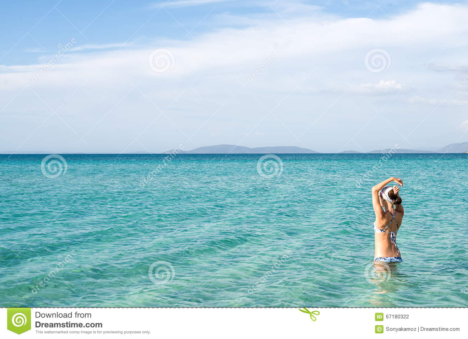 3dfdfc05e2b8 Back of beautiful woman in blue bikini standing in the water on  Mediterranean sea coast in Cesme