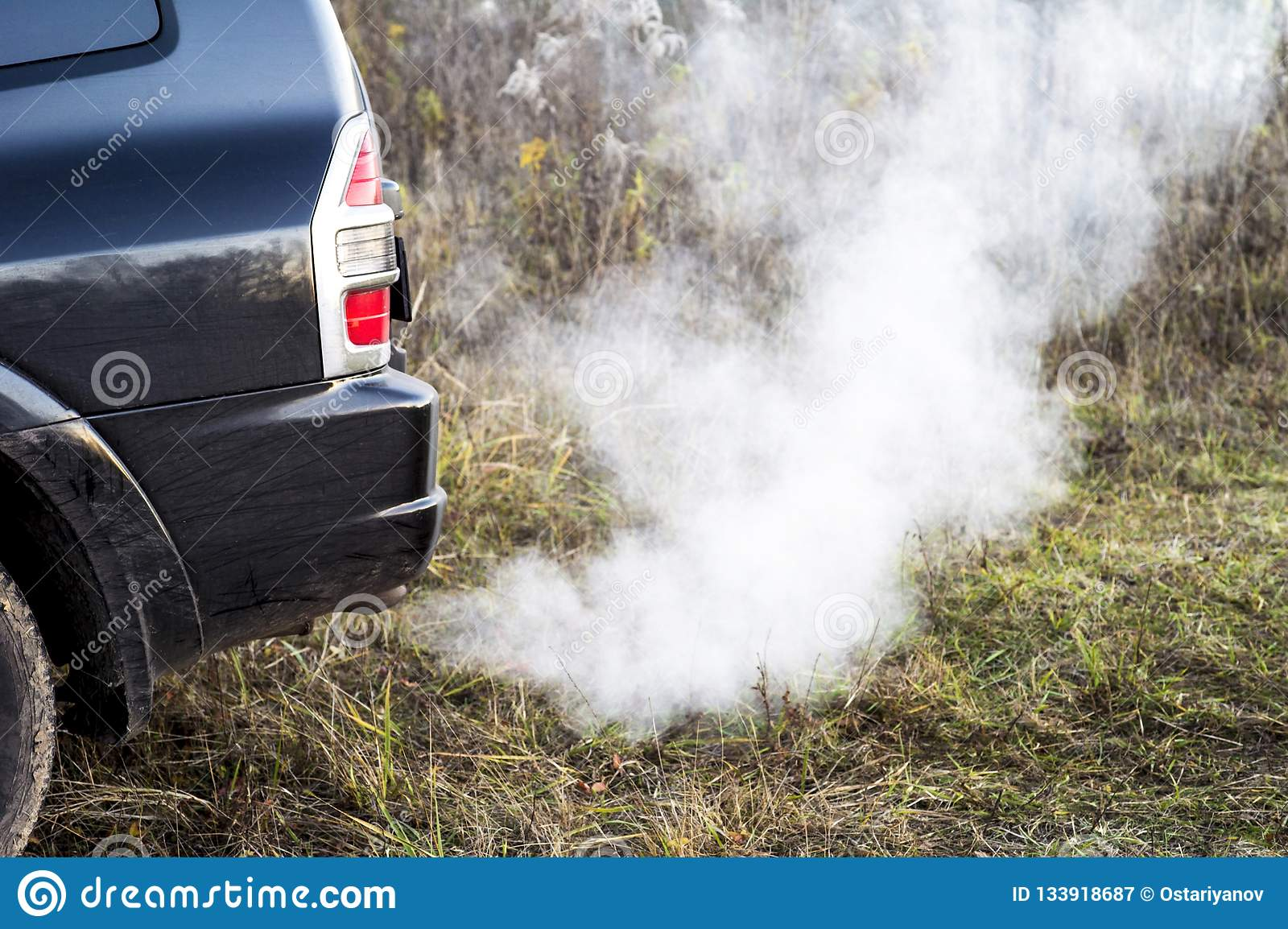 The back of the black car with the emission of smoke from the exhaust pipe on the background of nature
