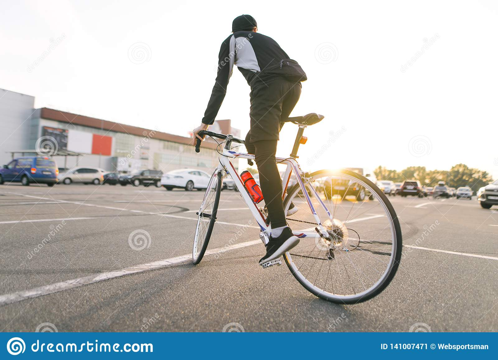 Back of a cyclist rides on a white highway bike on car parking, sunset and modern architecture on the background