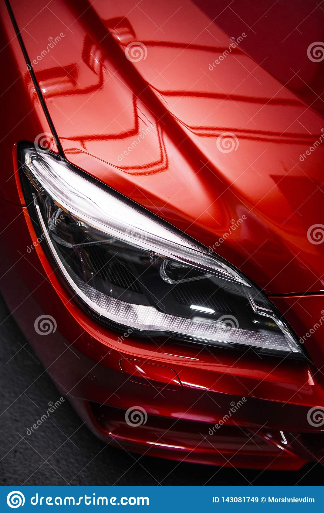 Back headlight of a modern luxury red car, auto detail, car care concept in the garage