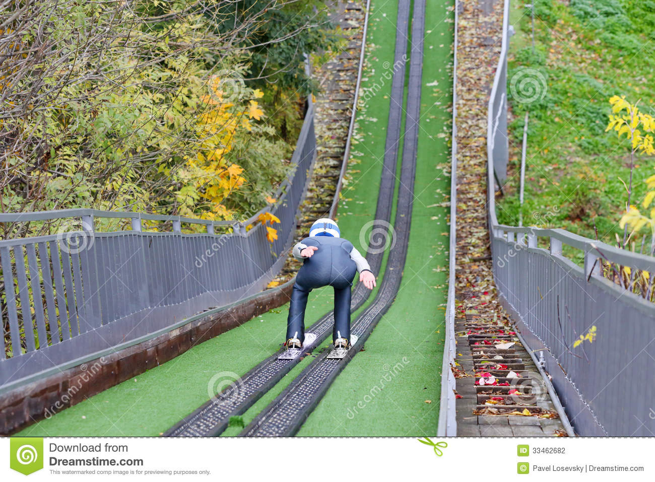 Back Of Man Descending From Artificial Hill On Skis Stock