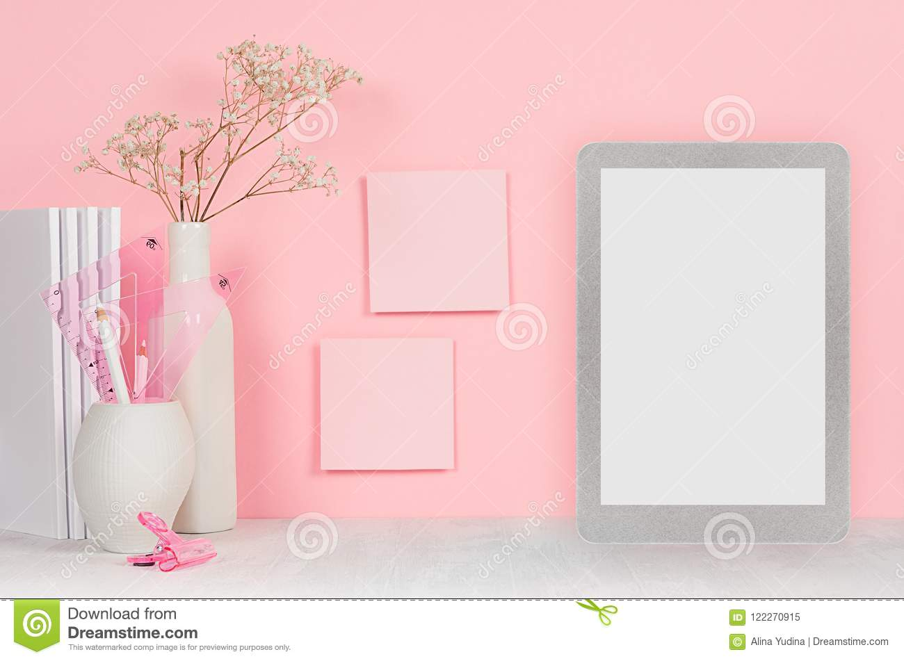 Back to school background for girl`s - white stationery, blank tablet computer and stickers on soft pink wall and white wood desk.