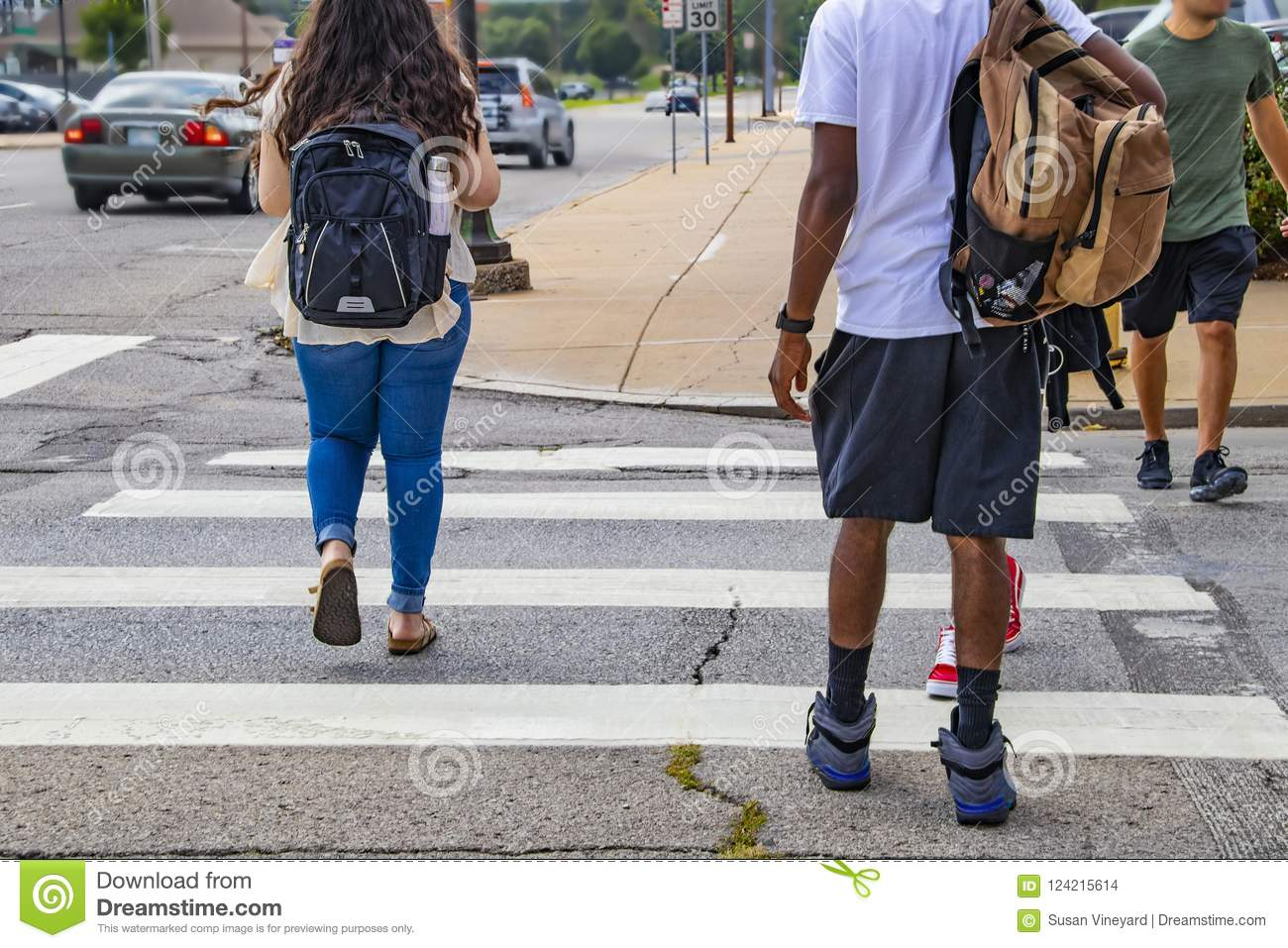 Back to school - the backs of college students crossing urban crosswalk with backpacks - ethnic diversity and casual dress with ca