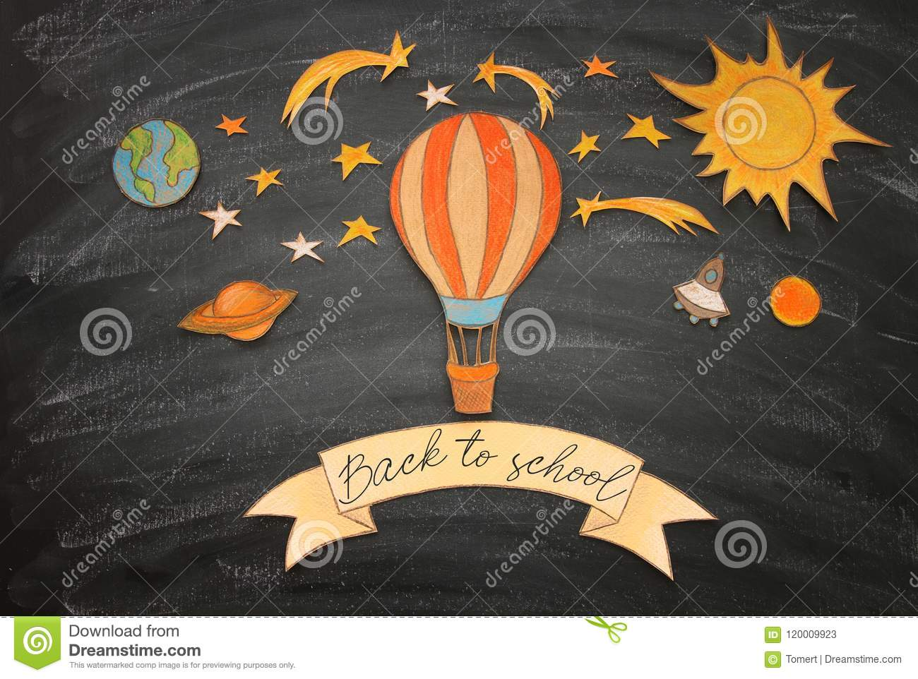 Back to school concept. Hot air balloon, space elements shapes cut from paper and painted over classroom blackboard background.