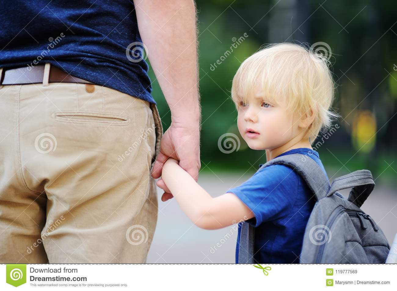 Back to school concept. Little pupil with his father. First day of primary school.