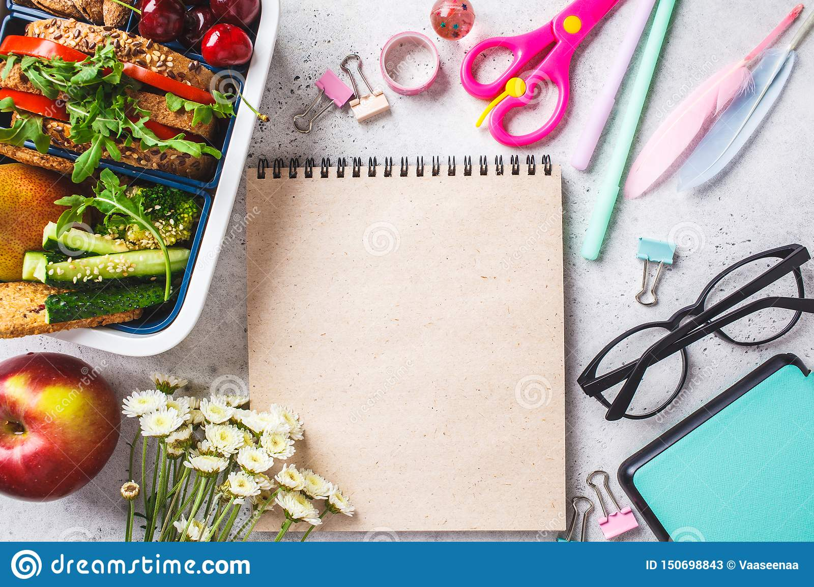 Back to school concept. Lunch box with sandwich, fruit, snacks, notebook, pencils and school items, top view