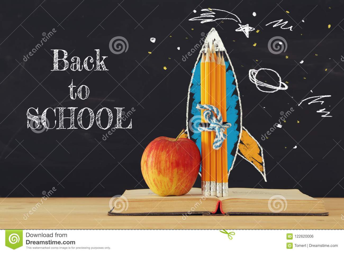 Back to school concept. rocket sketch and pencils over open book in front of classroom blackboard.