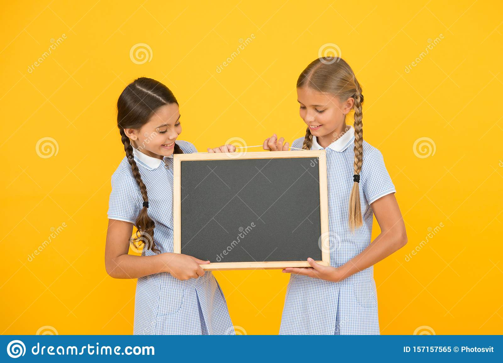 Back to school. small girls hold blackboard. children education. small girls presenting project. old school. copy space