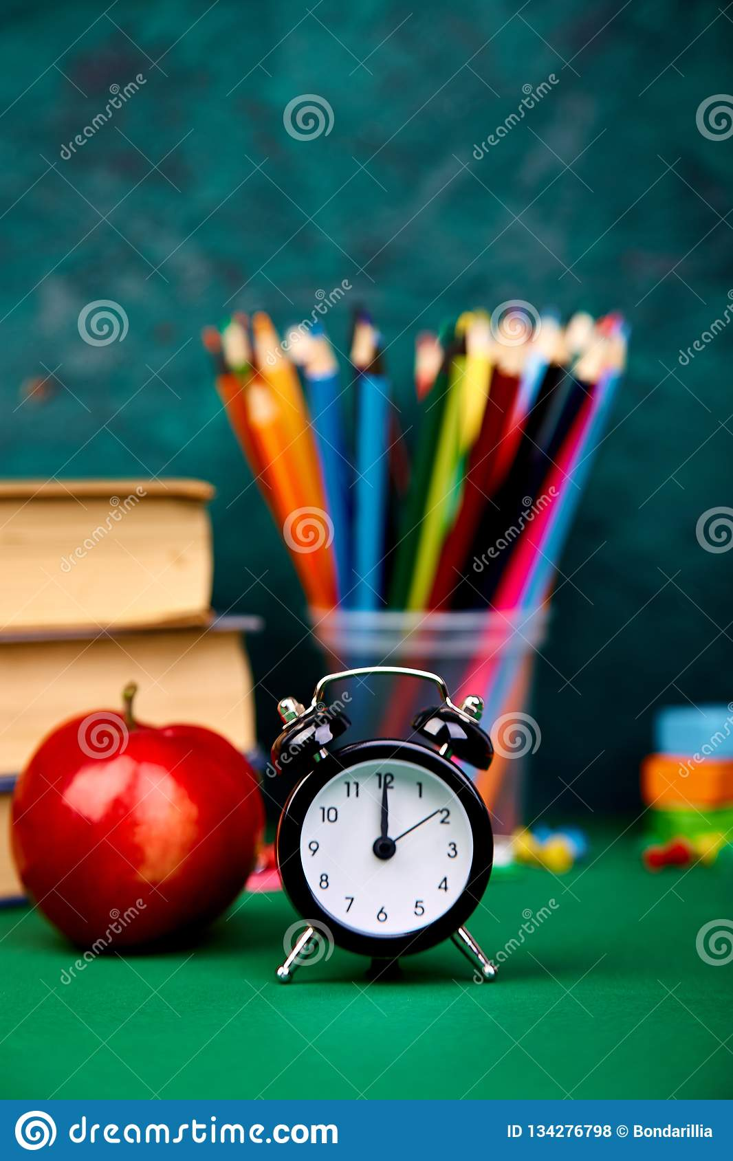 Back to school supplies. Books and red apple on green background