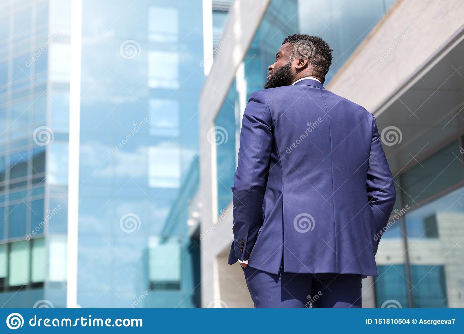 Back view of african american businessman walking along big office windows outdoors. Shot from back. Close up