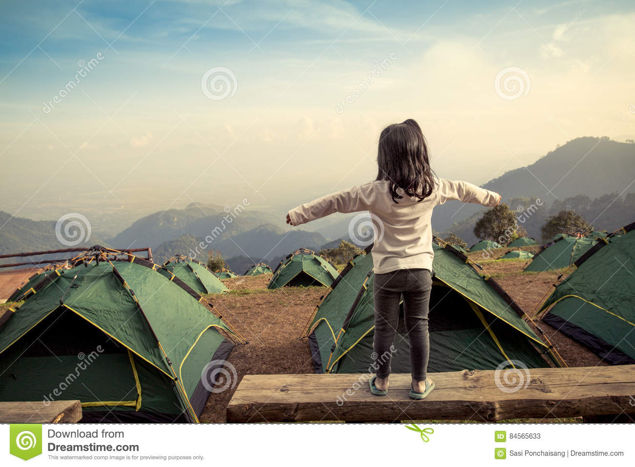 Back view of asian girl expand her arms in camping