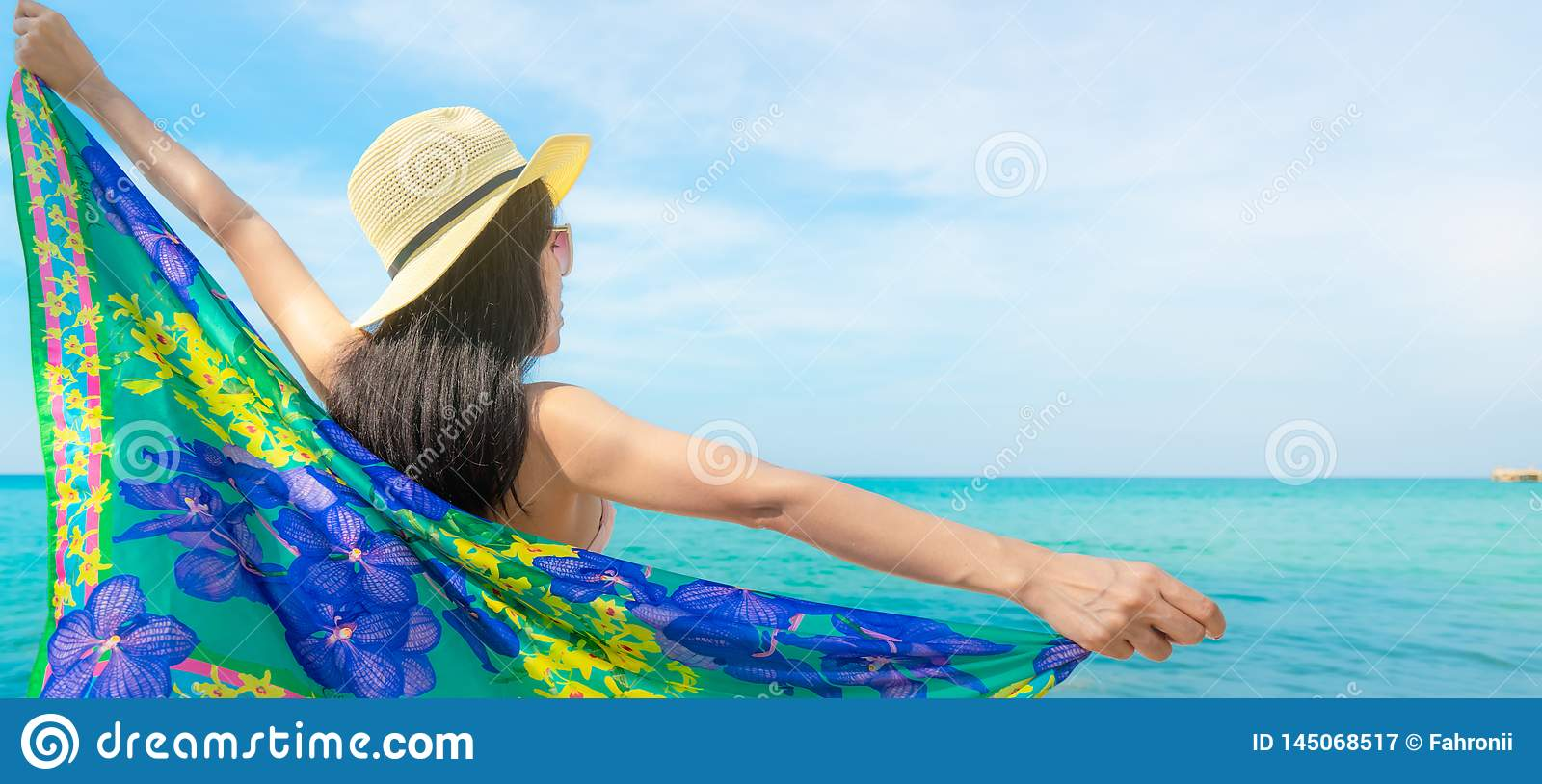 Back view of Asian woman wear swimsuit and opened arms at tropical beach on sunny day with beautiful blue sky and white clouds.