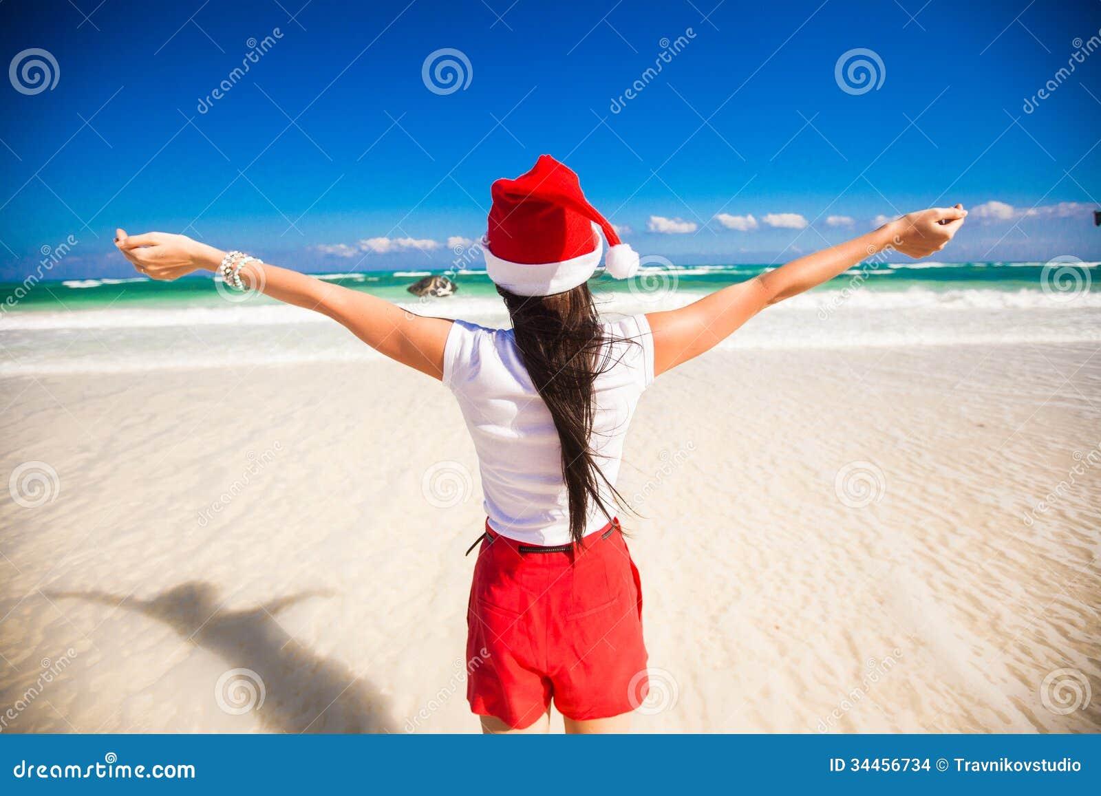 468025cfb55 Back view of beautiful girl in santa hat walking like a bird on white beach