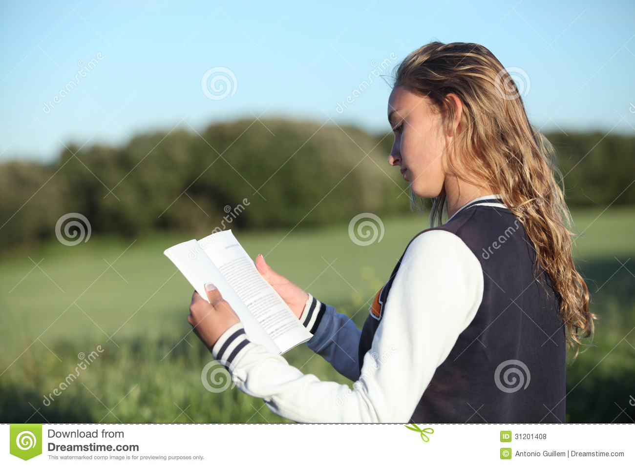 Back View Of A Beautiful Teen Girl Reading A Book Royalty