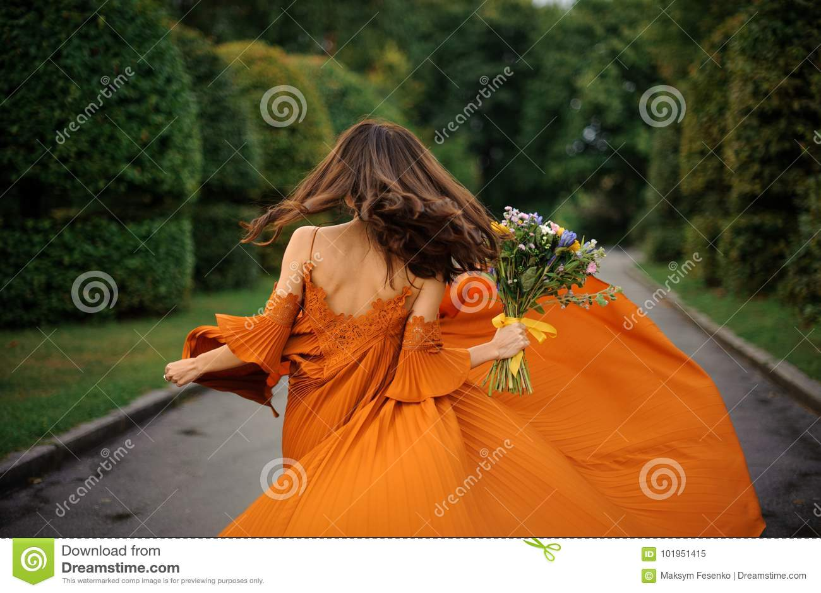 Back view of beautiful woman in long orange dress