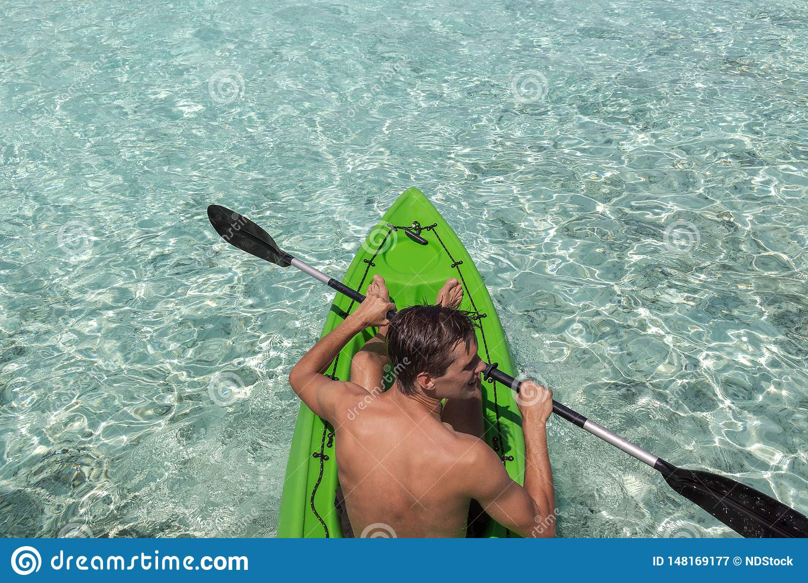 Young happy man kayaking on a tropical island in the Maldives. Clear blue water