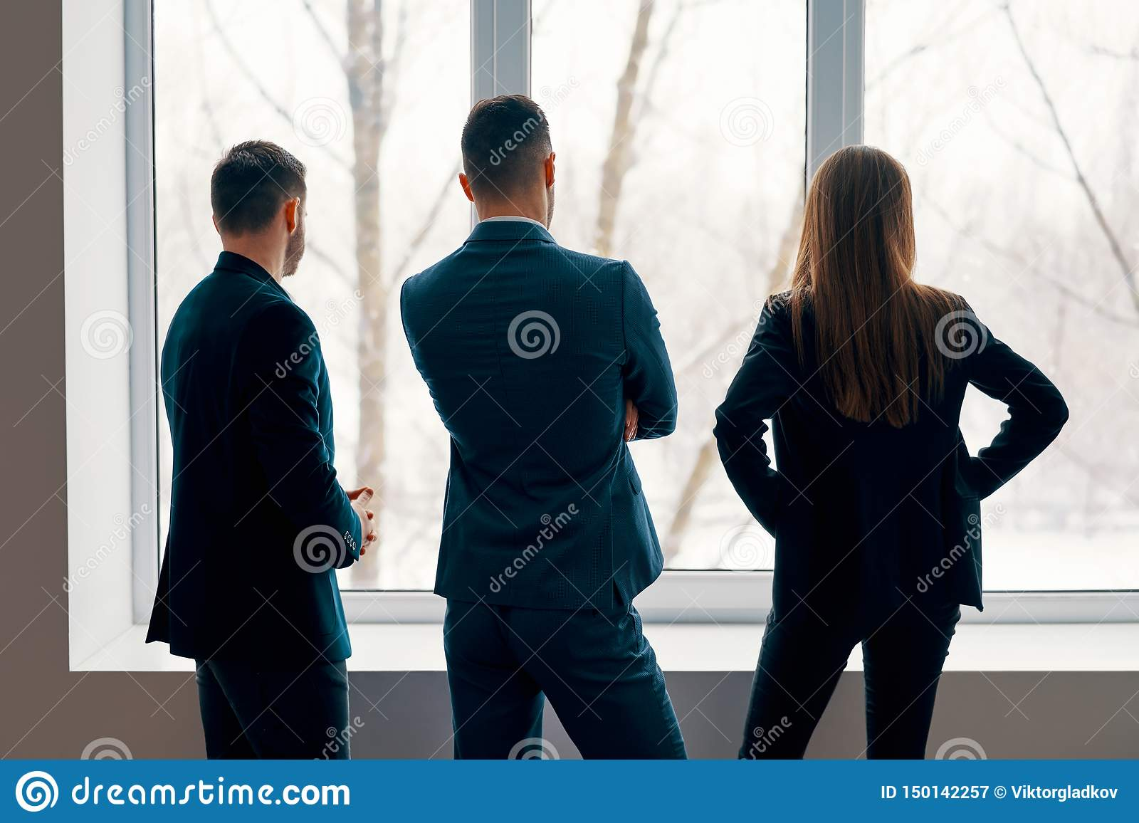 Back view of business people talking during the coffee break stand near the window in office