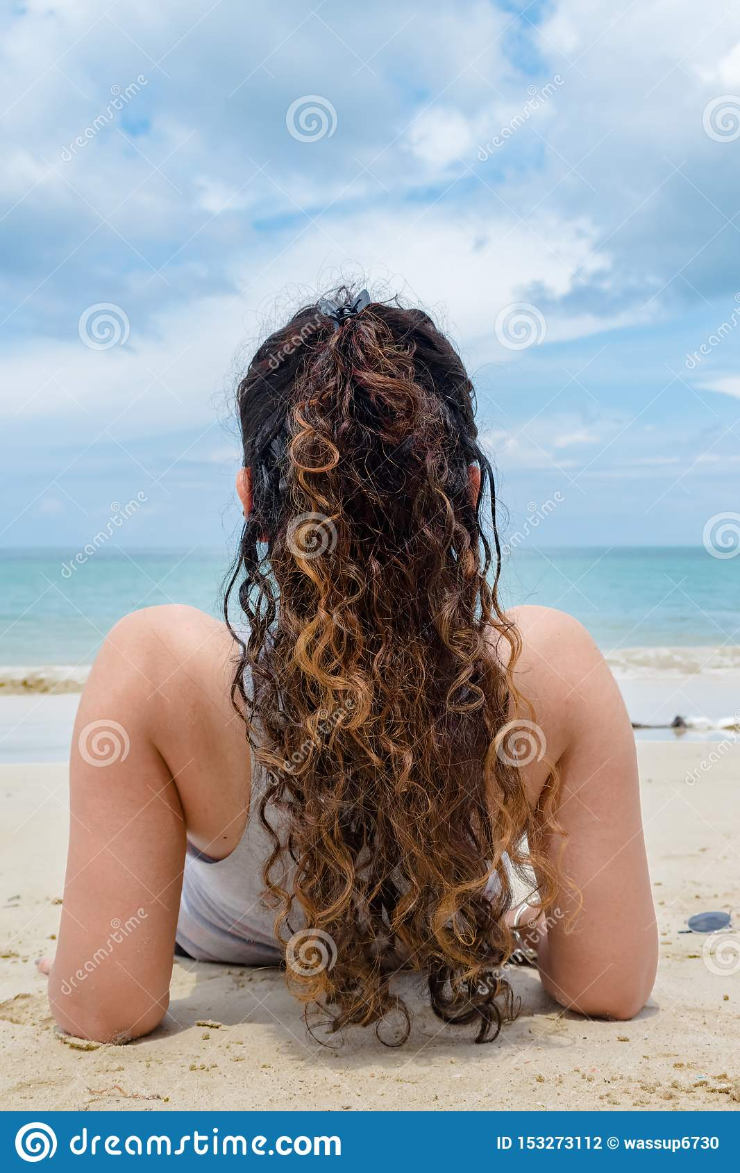 Back view of fair skinned Girl, having curly hairs of golden Color, relaxing & sunbathing solo on beach at exotic tropical island.