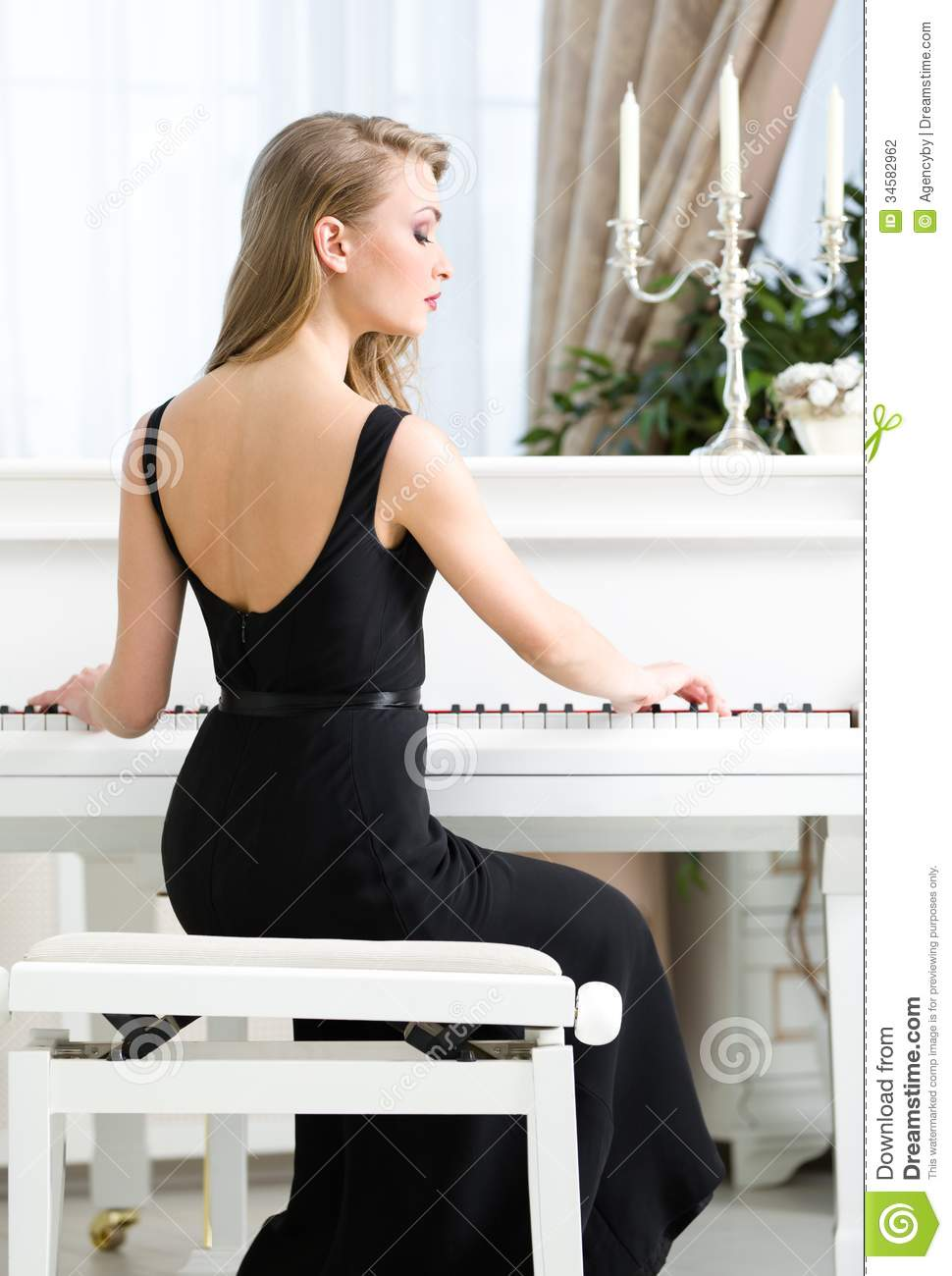 Back View Of Female Pianist Sitting And Playing Piano