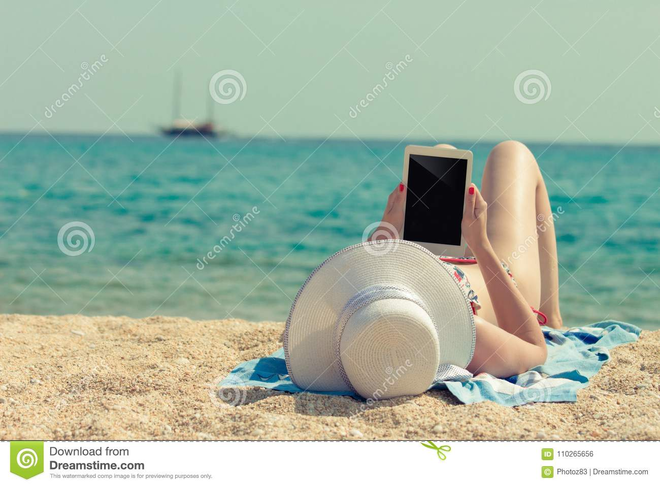 Female enjoying at the beach and holding blank screen digital ta