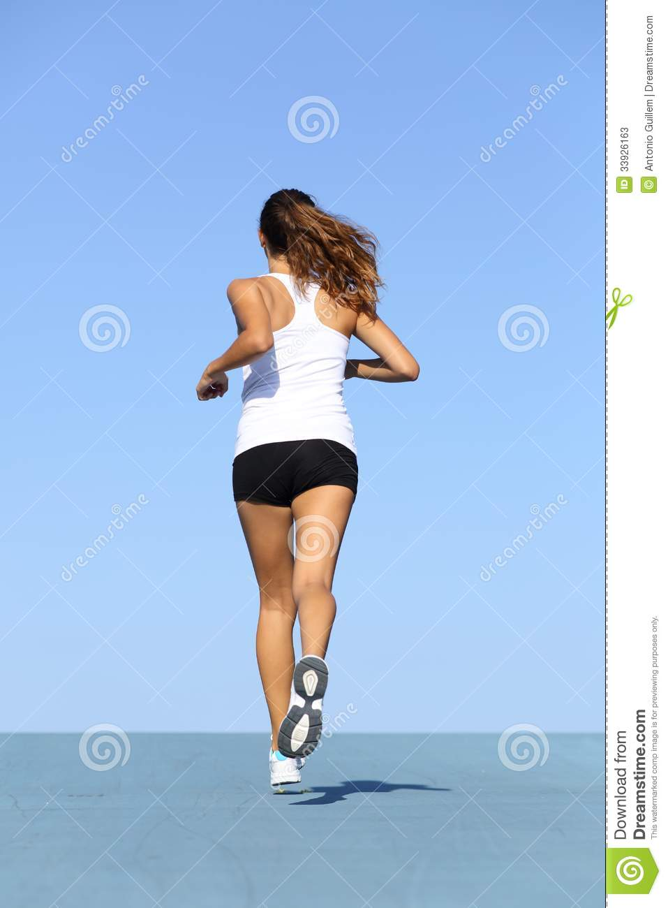 back view of a fitness woman running on blue stock photos