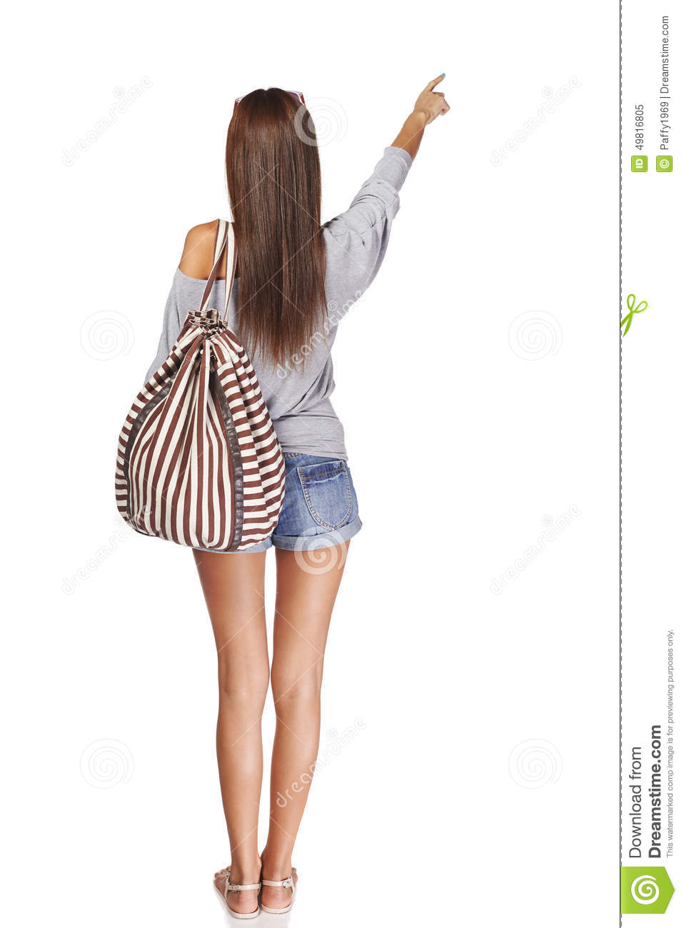 ac415e7c6c Back view Full length of young slim tanned female in denim shorts with backpack  pointing at blank copy space