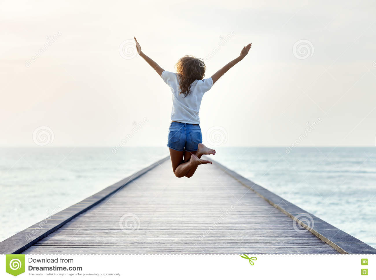 Back view of jumping girl on the pier