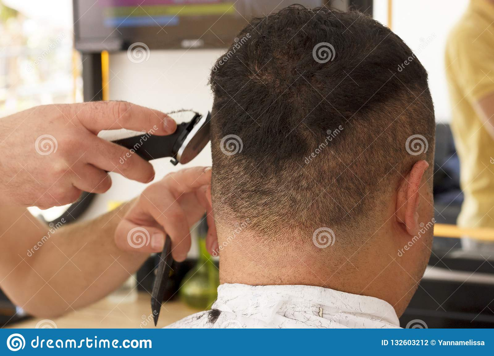 Back view of man getting short hair trimming at barber shop with clipper machine
