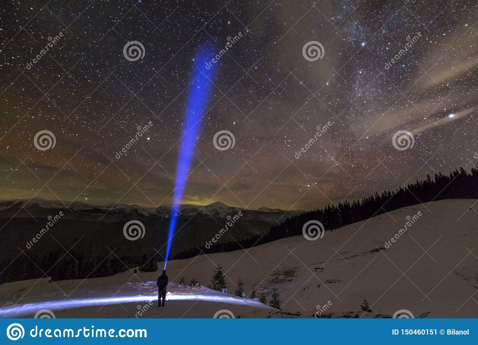 Back view of man with head flashlight standing on snowy valley under beautiful dark blue winter starry sky, bright blue beam on