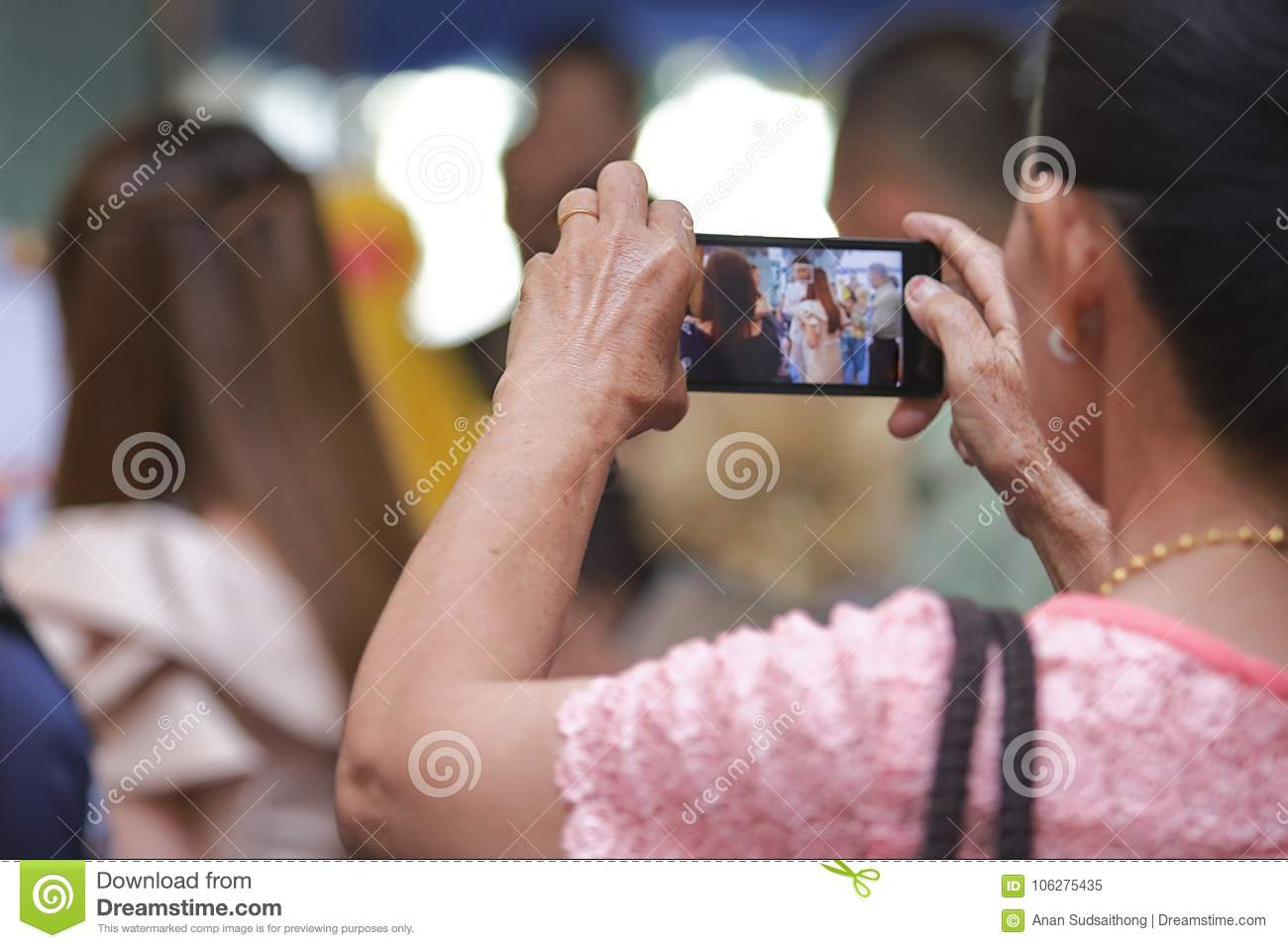 Back view of mobile smart phone is held against hands of senior Asian woman in luxury room background. Selective focus and shallow