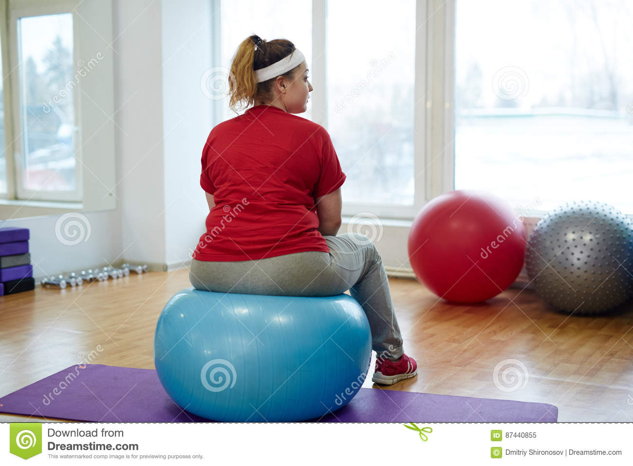 Back View Portrait of Obese Woman on Fitness ball