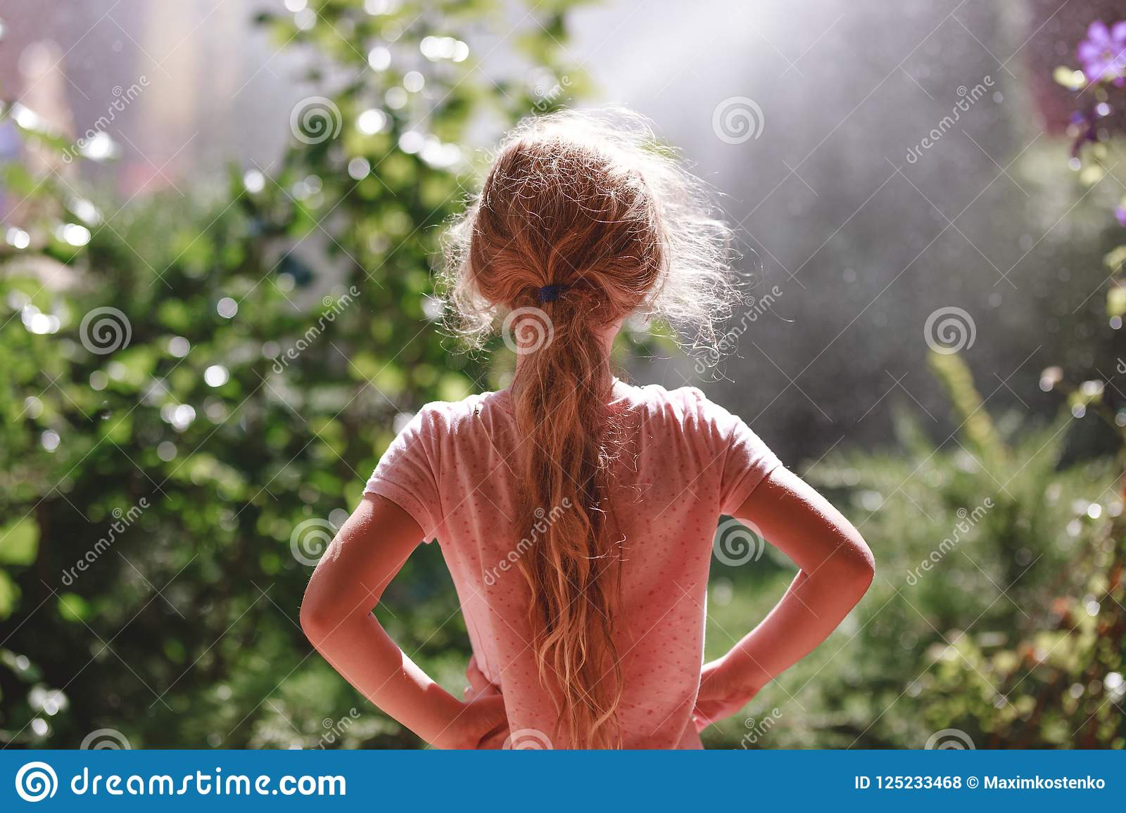 Back view of seven years old blonde girl wearing pyjamas standing outdoor in home garden in the early morning