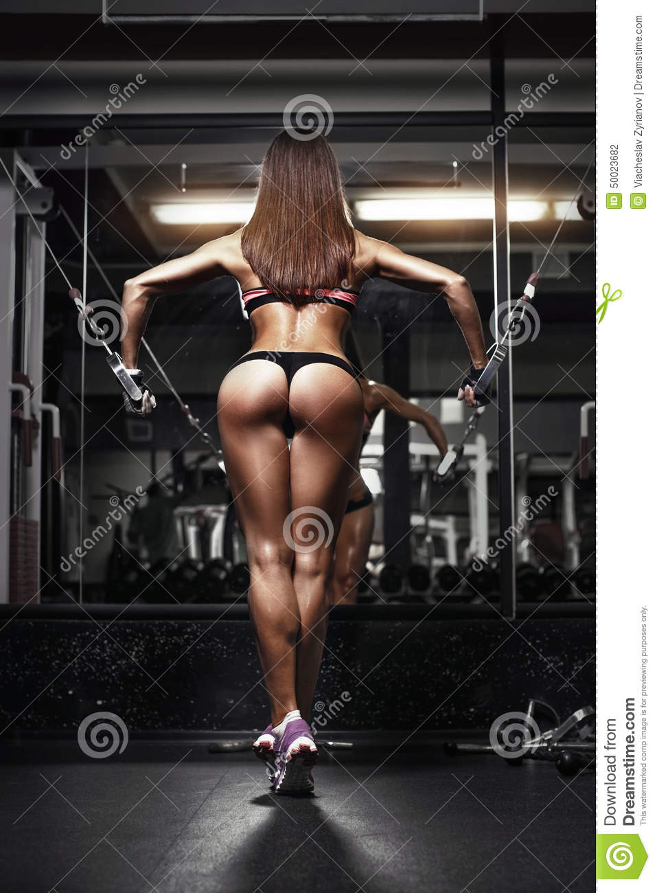 Back view of young brunette woman workout in the gym