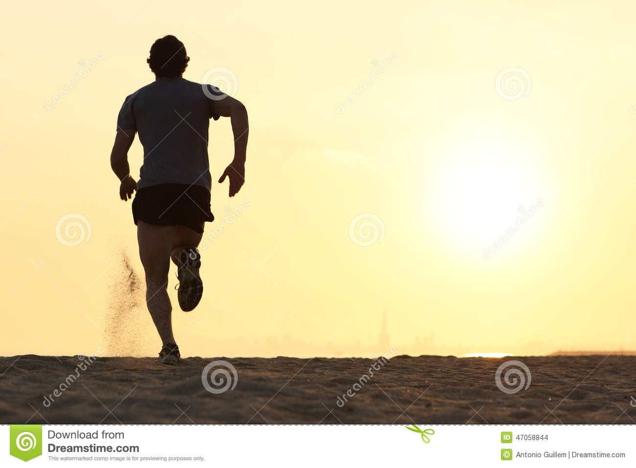 Back view silhouette of a runner man running on the beach