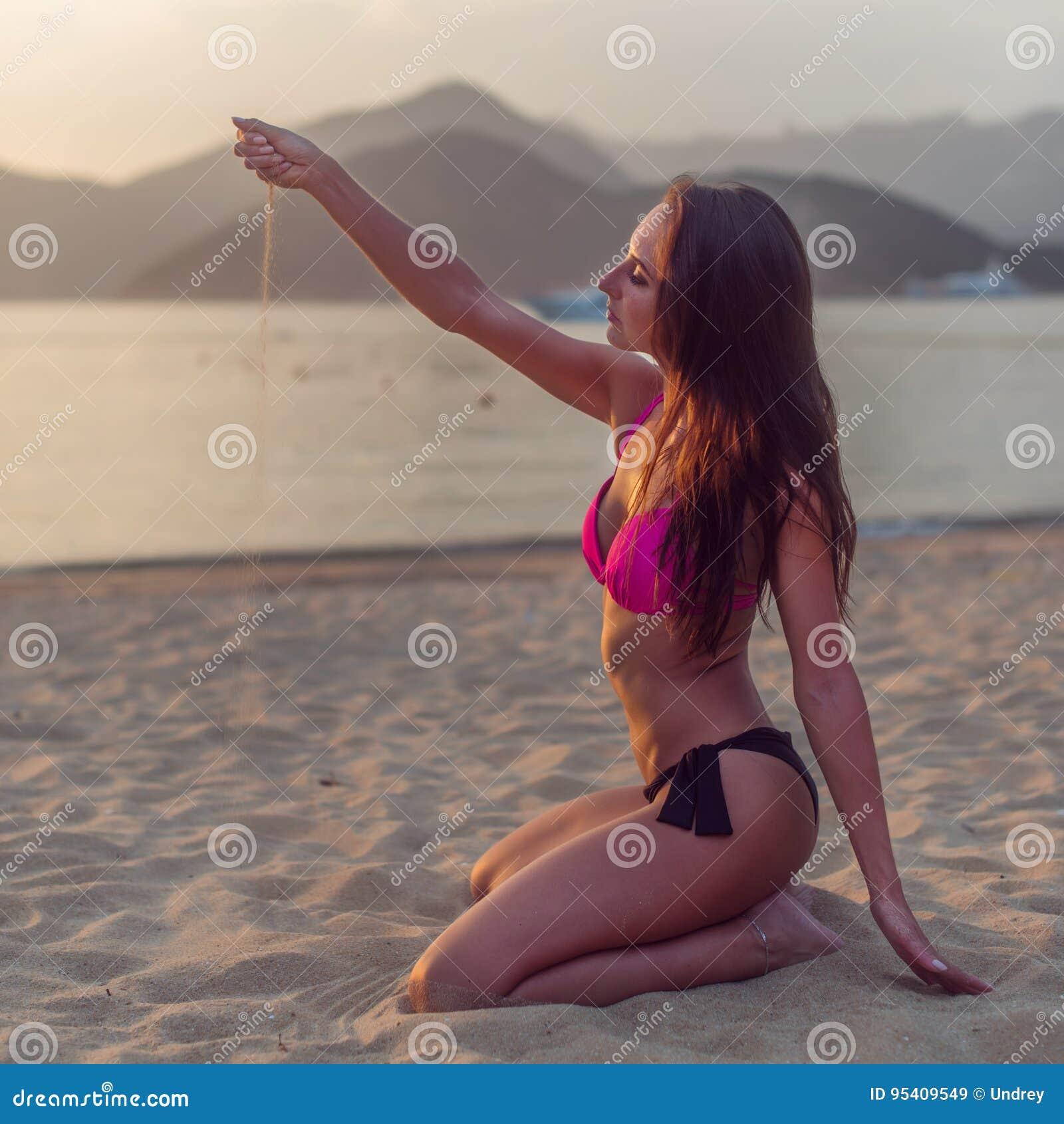 Back View Of Slim Brunette Young Woman In Bikini Sitting