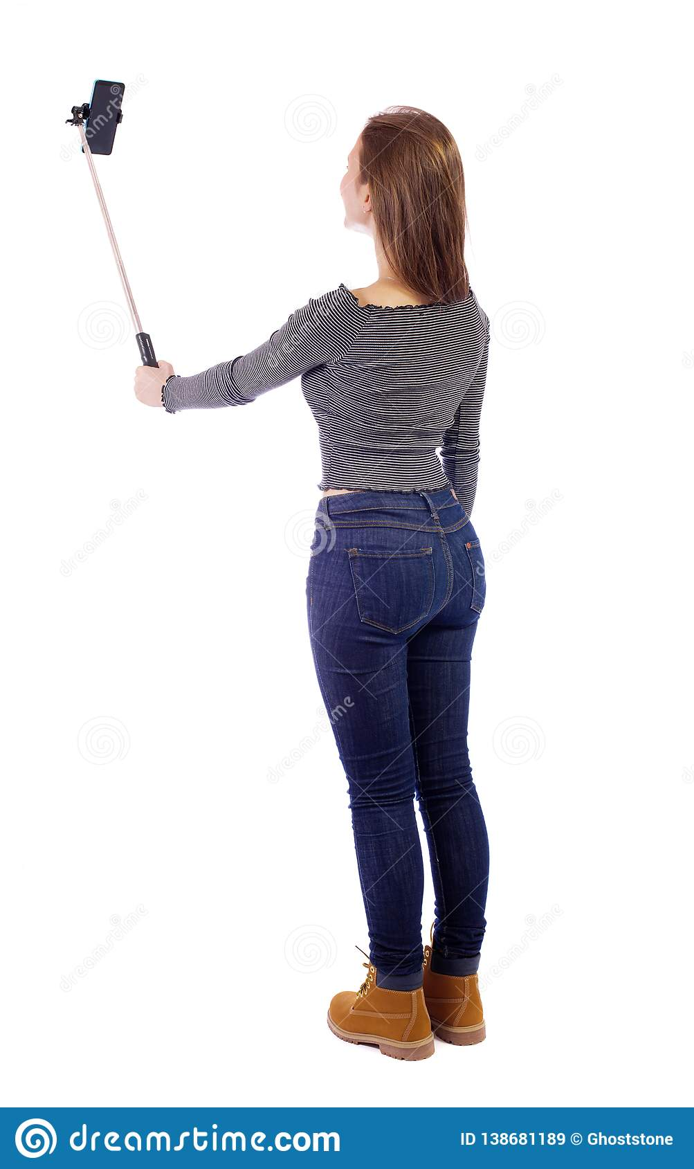 back view of standing young beautiful girl with smartphone in the hands of